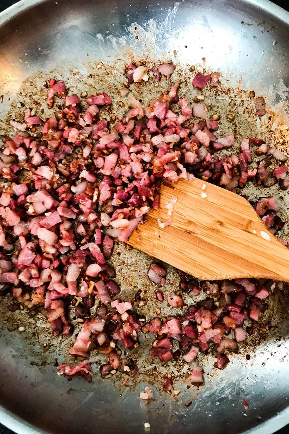 Cook the pancetta and garlic until lightly browned in a large skillet.