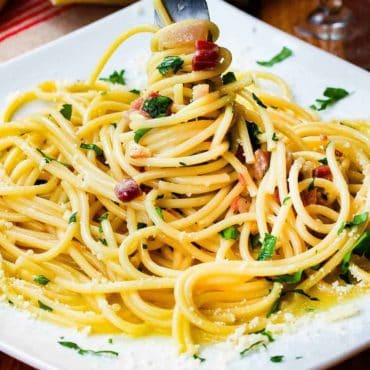 Twist the pasta carbonara with a fork on a serving plate.