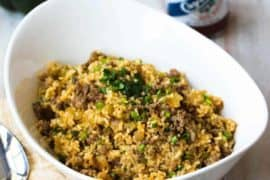Cajun Dirty Rice in a white bowl with chopped scallions on top
