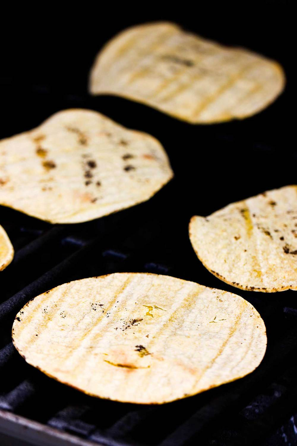 Corn tortillas heating up on a gas grill.