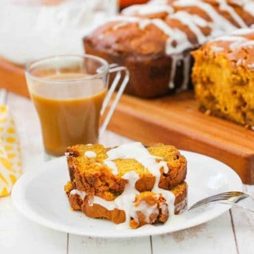 Two slices of pumpkin butterscotch bread on a white plate next to a cup of coffee.
