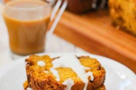 Two slices of pumpkin butterscotch bread on a white plate next to a cup of coffee and two loaves of bread.