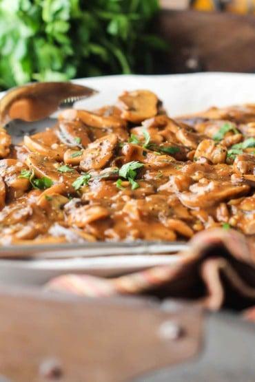 A white platter with Chicken Marsala