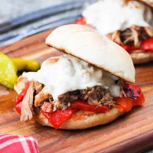 Instant Pot Italian Pulled Chicken Sandwich on a wooden cutting board with a knife and fork next to a patterned red napkin