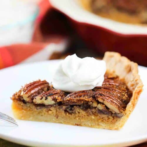 A slice of Classic Pecan Pie topped with whipped cream on a white plate