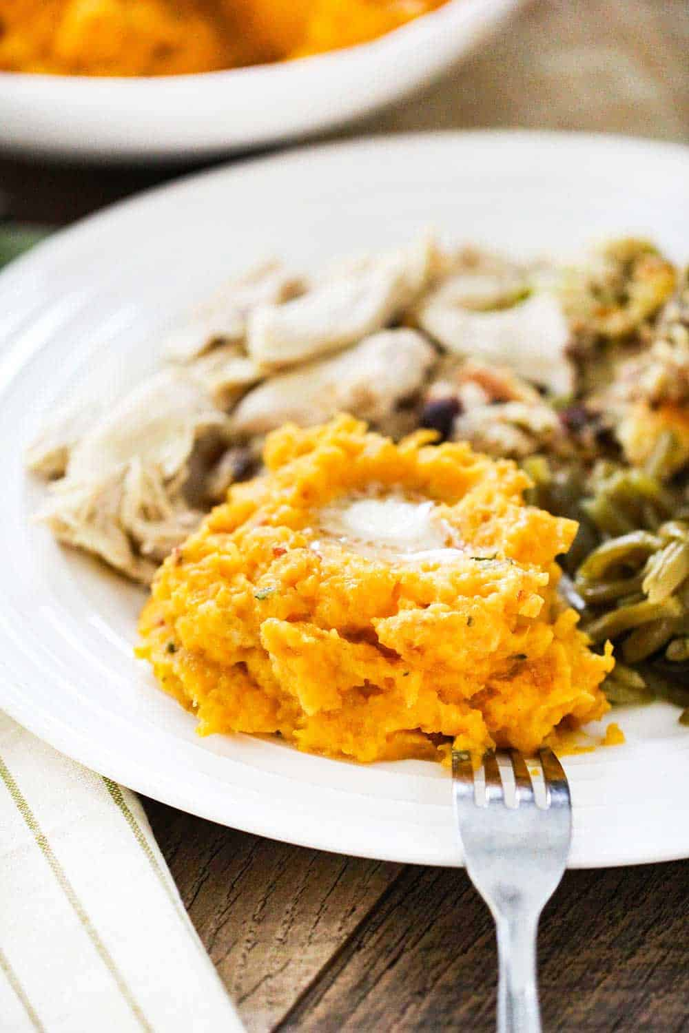 A plate of mashed butternut squash topped with butter, next to roasted turkey, stuffing and green beans.