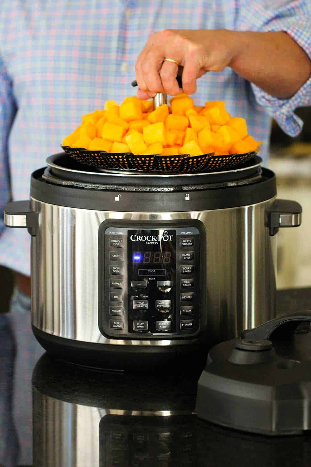 A hand lowering a steamer basket holding cut butternut squash into a 10 qt. pressure cooker.