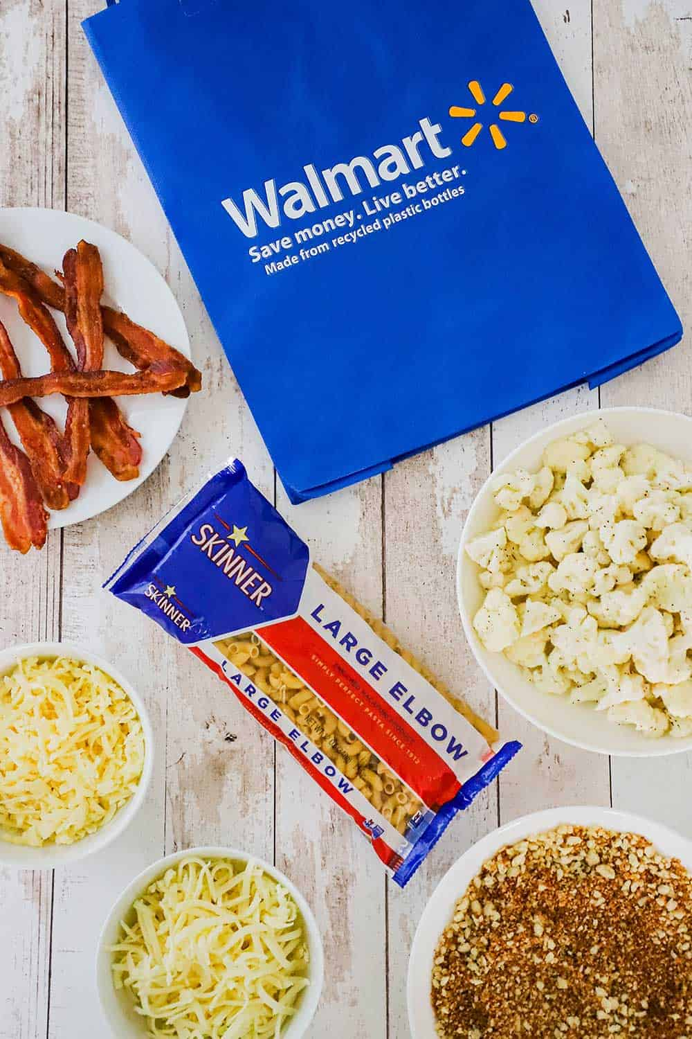 A large blue Walmart bag on its side next to a plate of cooked bacon, a bag of Skinner pasta, and bowls of cheese and bread crumbs.
