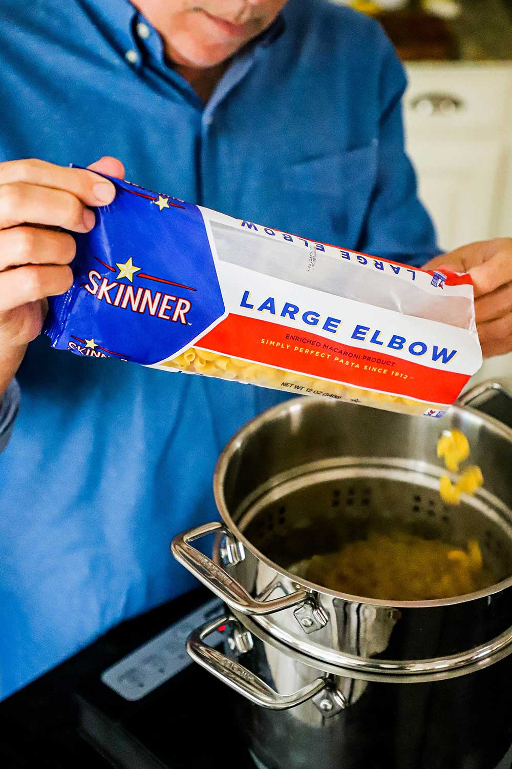 A man pouring elbow pasta from a bag into a pasta pan filled with boiling water.