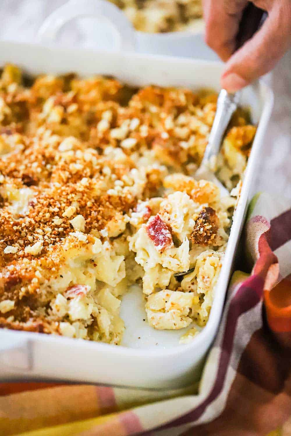 A person using a spoon to scoop out a helping of macaroni and cheese with cauliflower and bacon out of a white square baking dish.