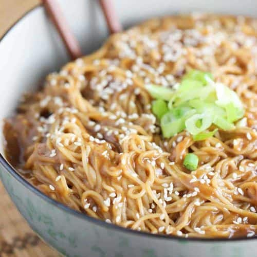 Chinese noodles with peanut sauce in a bowl with chopsticks