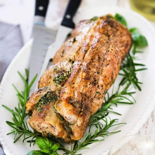 Herb stuffed pork loin being drizzled with gravy on a wooden cutting board.