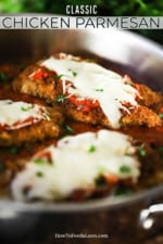 Three chicken parmesan cutlets sitting in a large silver skillet filled with marinara sauce.