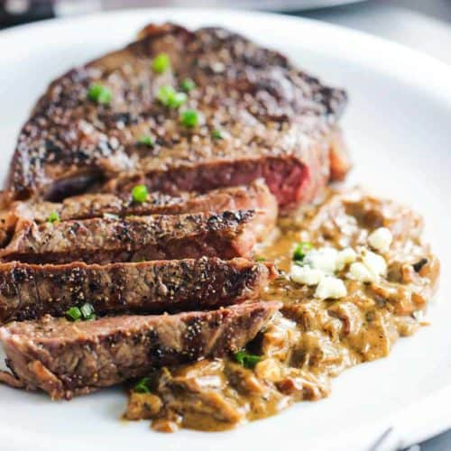 Ribeye with Gorgonzola and Caramelized Onion Sauce on a white plate next to a fork and knife