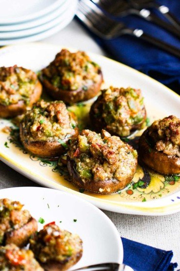 A platter filled with sausage-stuffed mushrooms next to a plate of the same.
