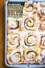 A metal baking pan filled with homemade cinnamon rolls with a roll missing from the lower left-hand corner.