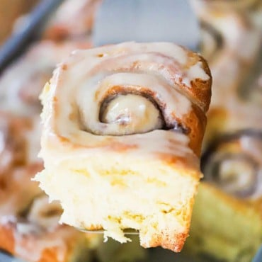 A hand holding a spatula with a homemade cinnamon roll on it over a pan of the rolls.