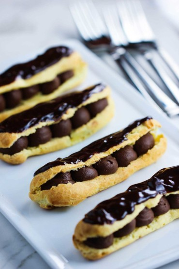 Chocolate Eclairs on a white plate next to silver forks