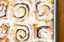 A 9 by 13-inch metal baking pan filled with homemade cinnamon rolls with one in the lower right corner missing.