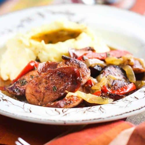 A bowl of Beer-Braised Kielbasa with Peppers next to a patterned napkin and fork