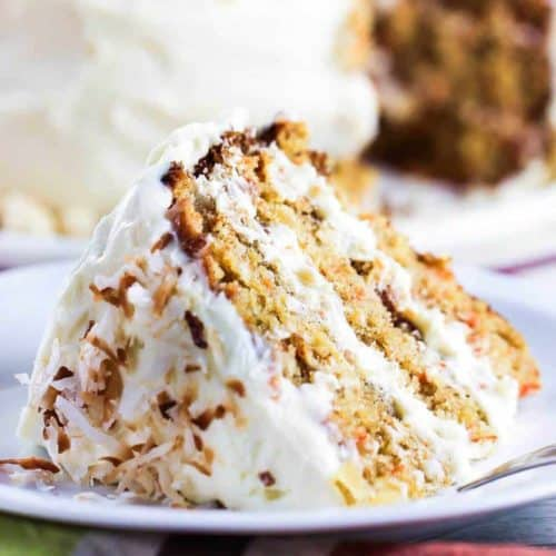 A slice of Carrot Cake with Coconut, Ginger and Macadamia Nuts next to a patterned napkin