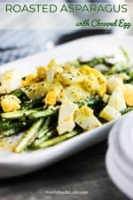 An oval white platter filled with roasted asparagus topped with chopped hard-boiled eggs.