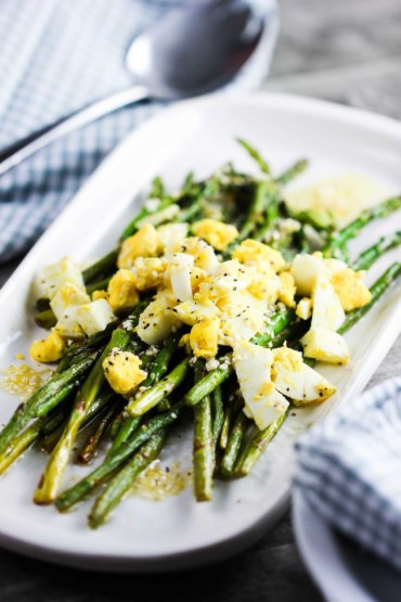 Roasted asparagus, sesame and chopped egg salad on a white dish next to a blue and white checkered napkin with a spoon on top