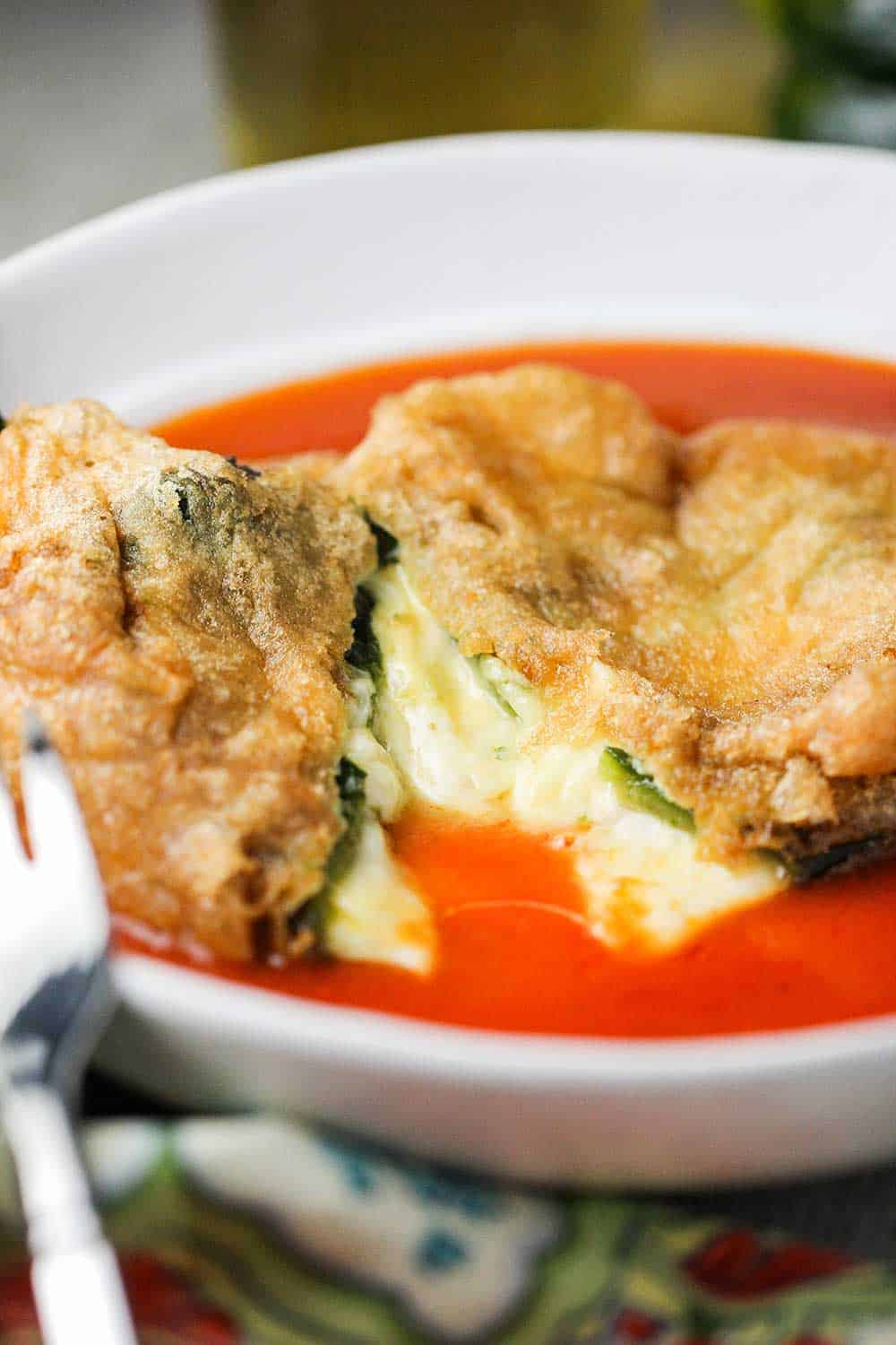 Chile rellenos that is cut in half in a white bowl.