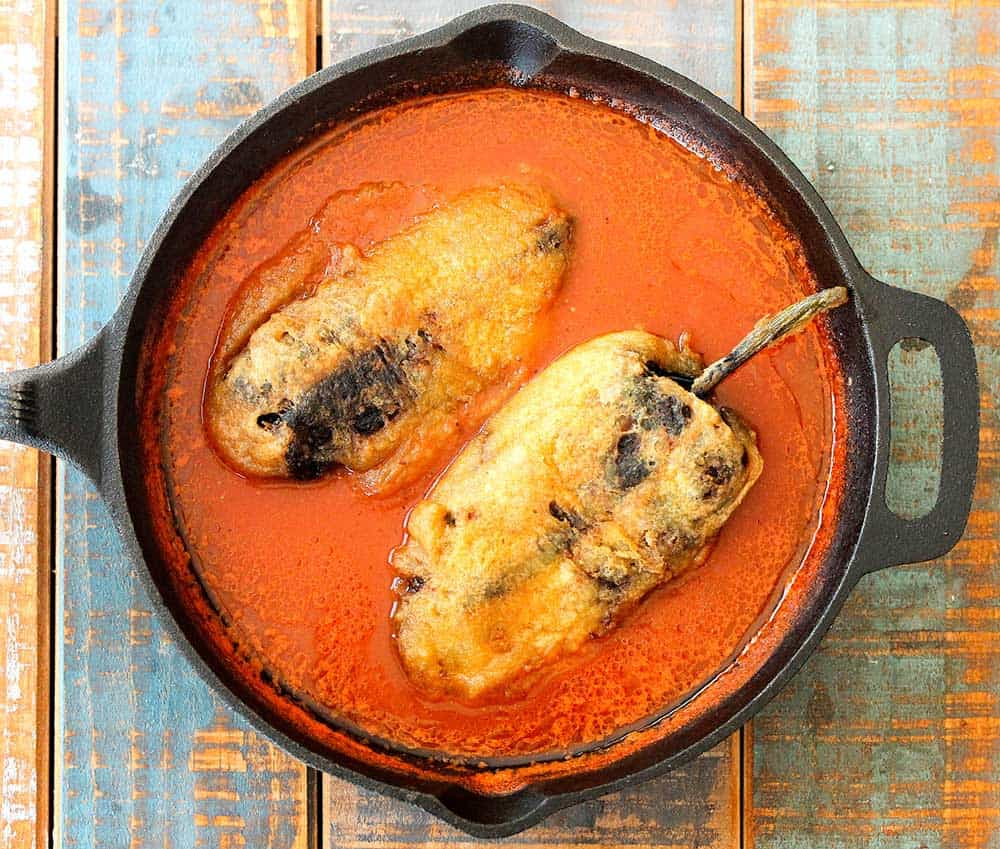 Chile rellenos in a cast iron skillet.