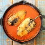 Chile rellenos in a black cast iron skillet.