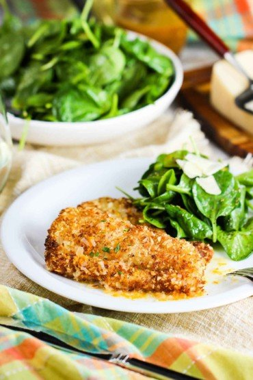A white plate with almond crusted cod and spinach next to a bowl of spinach and a patterned napkin.