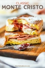 A Monte Cristo sandwich that has been sliced in half and then stacked, with a smear of preserves in the middle and a bite taken out.