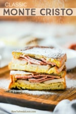 A Monte Cristo sandwich that is cut in half and stacked and powdered sugar sprinkling