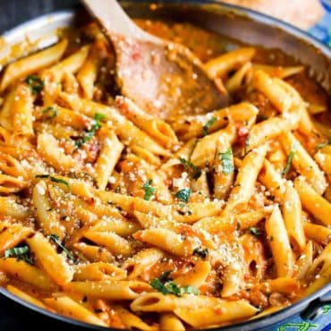 Penne alla vodka in a large skillet with a wooden spoon.