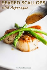 A spoon pouring a brown sauce onto several seared scallops topped with sautéed asparagus.