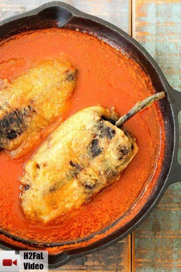 Two Chile rellenos in a red sauce in a cast iron skillet