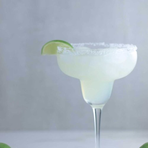 A margarita glass with Mama's Classic Margarita with a slice of lime next to limes