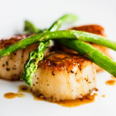 A white dinner plate filled with seared scallops topped with sautéed asparagus topped with a brown sauce.
