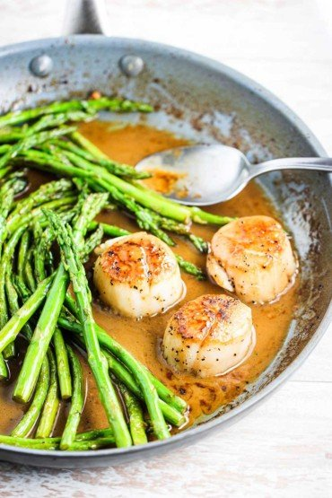 A skillet filled with 3 seared scallops with asparagus in a white wine brown sauce.