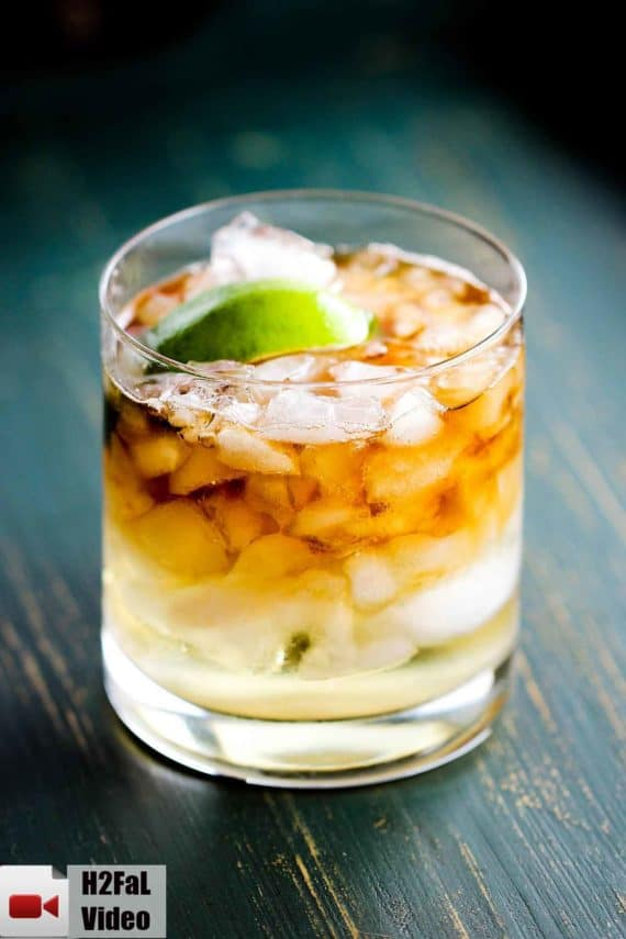 This is a dark and stormy cocktail with chipped ice, rum, ginger beer and a lime in a rocks glass.