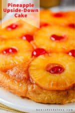 A close up view of a pineapple upside-down cake on a white platter.