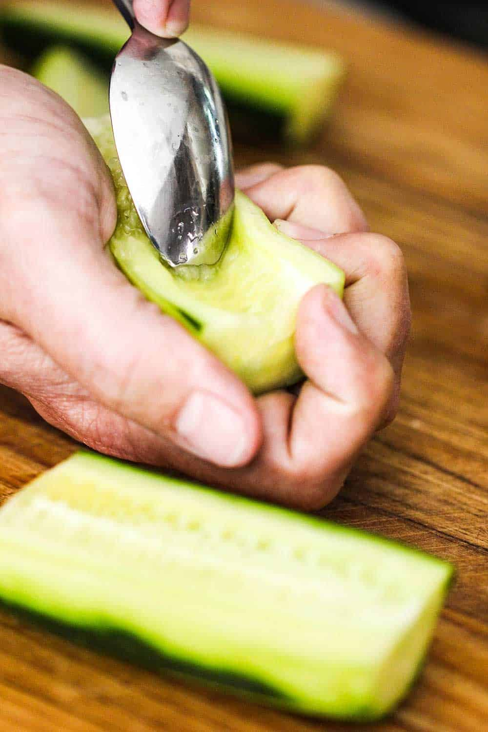 Use a spoon to scoop out the seeds of the cucumber.