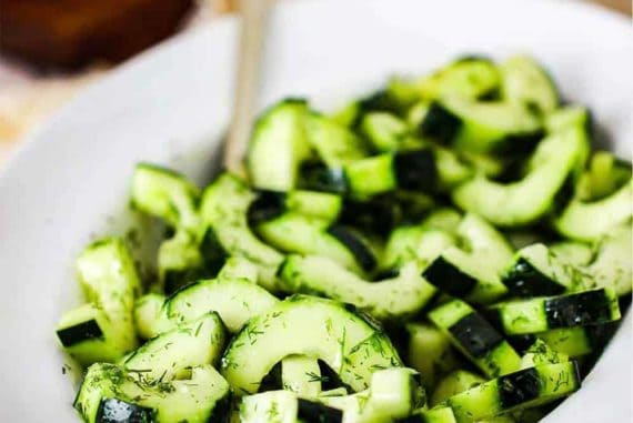 A white bowl of cucumber and dill salad with a gold serving spoon.