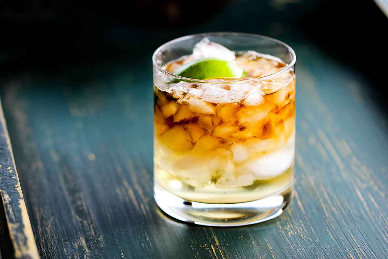A glass with a dark and stormy cocktail in it garnished with lime.