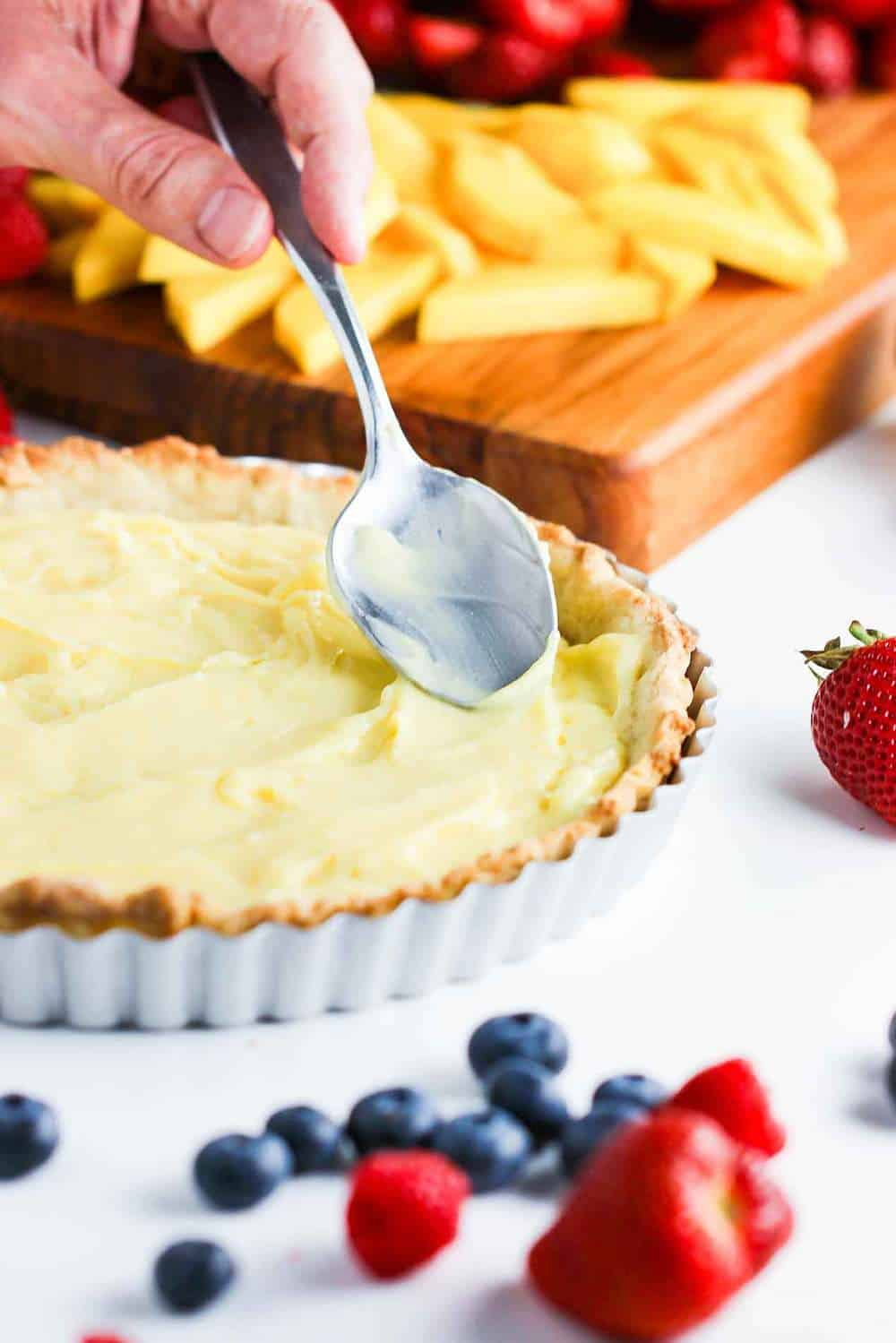 filling the fruit tart shel with pastry cream