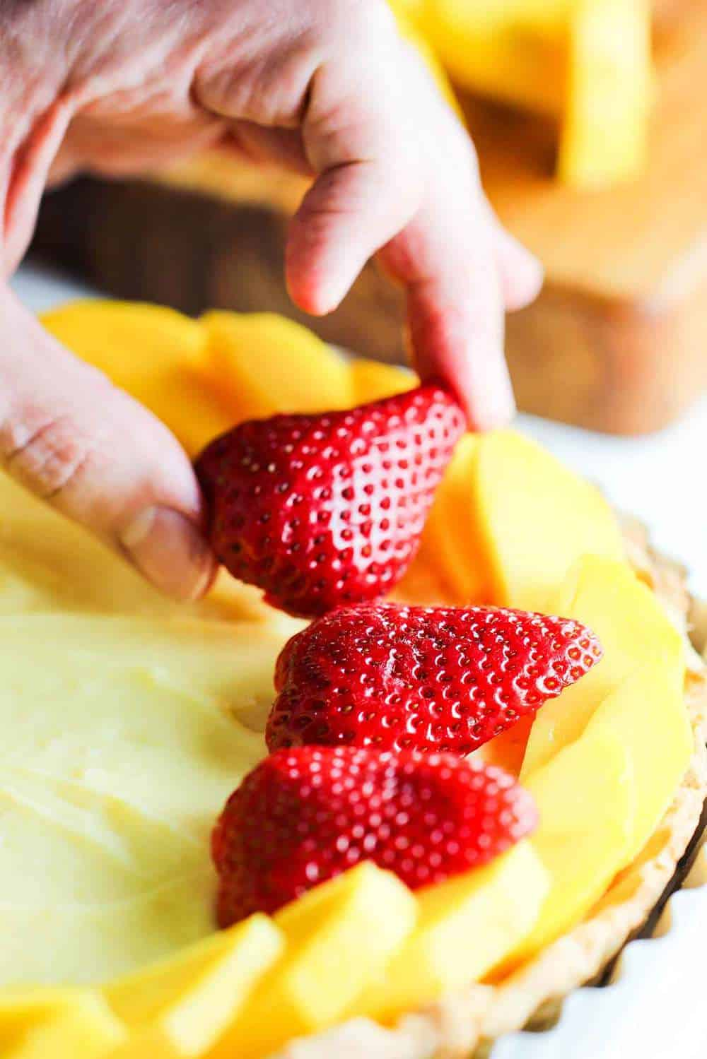 adding strawberries to the classic fruit tart
