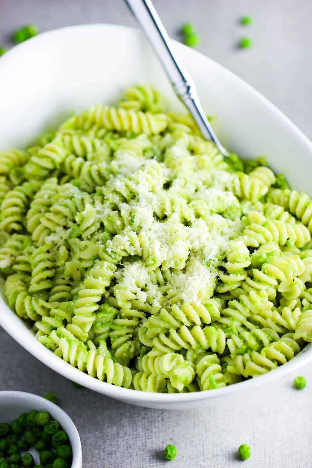 Fresh pea pesto pasta in a white serving bowl with a spoon