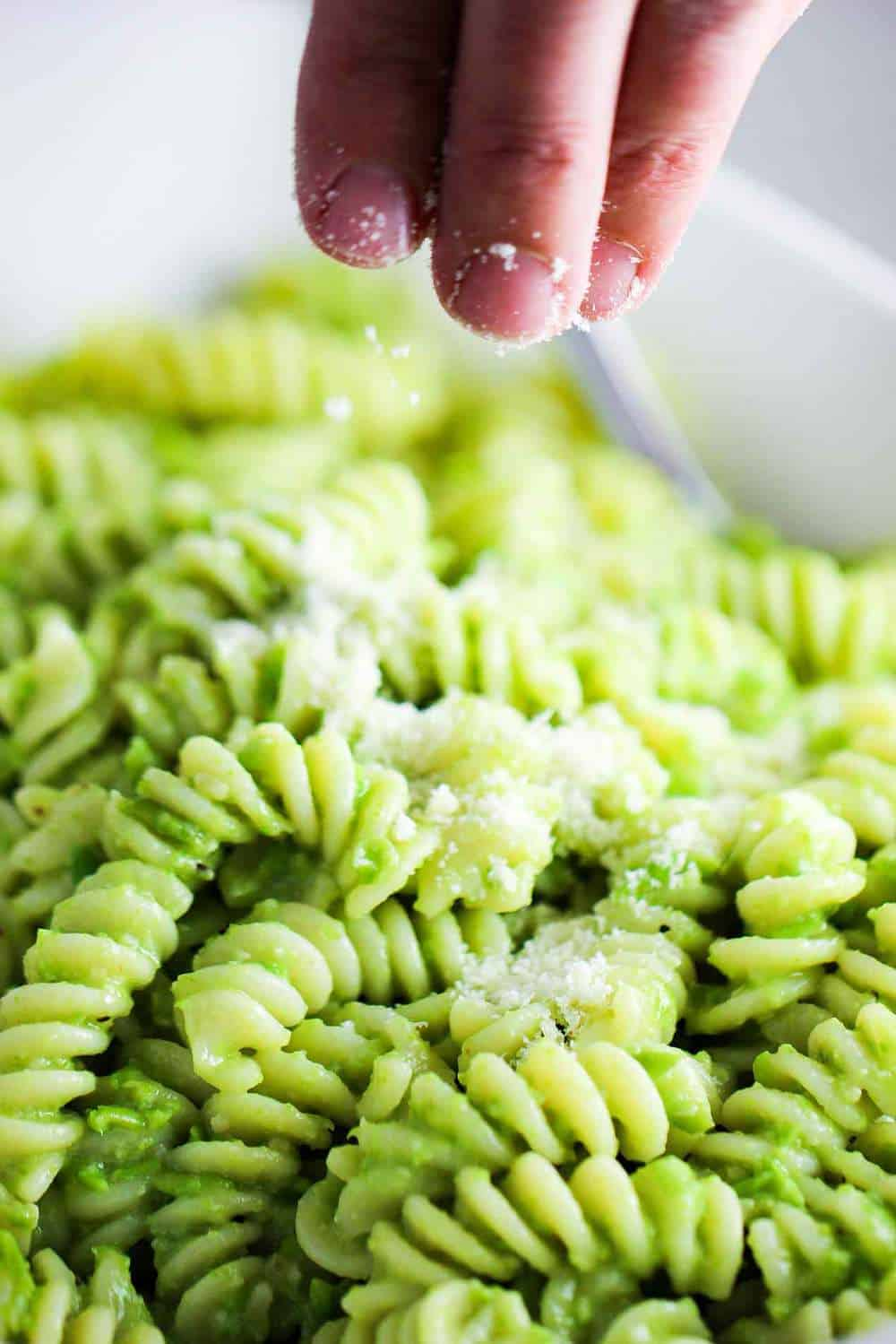 Fingers sprinkling grated Parmesan cheese over a bowl of pea pesto pasta