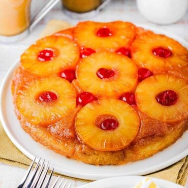 A pineapple upside-down cake on a white platter next to a glass of orange and a cup of coffee.