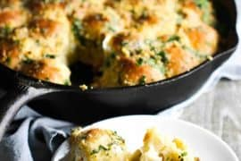 Cheesy skillet rolls in the background in a cast iron skillet with a single roll on a plate in front